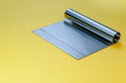 Metal dough scraper knife over bright yellow surface background. Stainless steel flat dough scraper with Ruler scale. Grid cm, inch. Size indicator units. Metric Centimeter, inch size indicators.