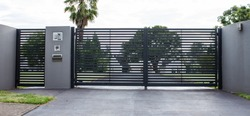 Metal driveway property entrance gates set in concrete fence with garden trees  in background