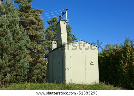 Metal electric building on a trees and blue sky background