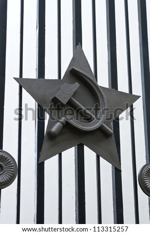 Metal emblem on the gate -  star, hammer, sickle