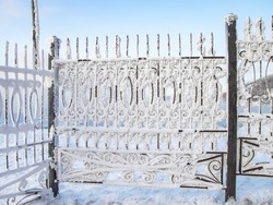Metal fence covered with snow and frost in the city Park. Extremely cold winter
