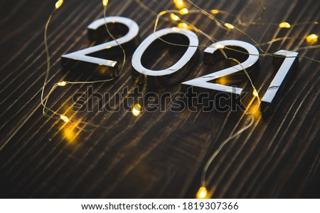 metal figures 2021 with a garland on a ninth background. new years eve