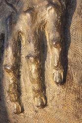 Metal fingers of a bronze sculpture with artificial lighting