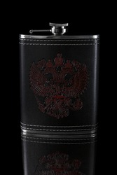 Metal flask in a leather case with a pattern depicting a doubleheaded eagle on a black background