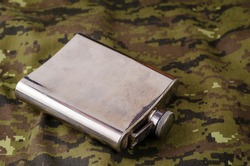 Metal flask on camouflage fabric. Shiny stained flask for various drinks on military uniforms. Army theme or hunting. Selective Focus.