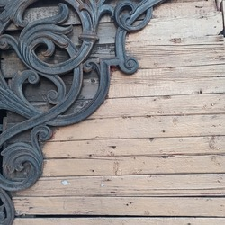 Metal forging. Corner forged decor. Decorative architectural element. Wooden slats. Place for your text. Horizontal background.