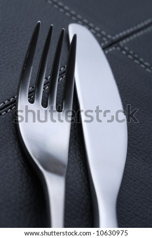 metal fork and knife with abstract blue light, on black leather place mat