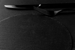 metal fork, knife and round empty black plate from slate stone close-up. dark textured cement background, copy space