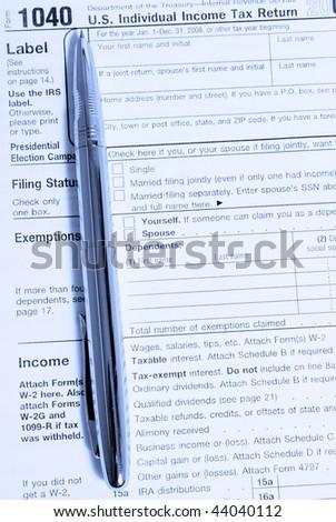 metal fountain pen on 1040 tax form in blue light