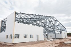 Metal frame of the building with a sandwich panel of insulation on the wall. The use of modern building materials