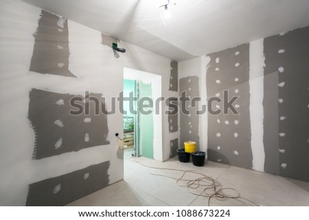 Metal frames and plasterboard -drywall- for gypsum walls, three buckets and electric wires  in apartment is under construction, remodeling, renovation, extension, restoration and reconstruction #1088673224