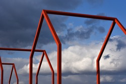 Metal frames of void houses without roofs and walls against the gloomy sky