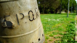 Metal garbage bin in a park engraved with the word SPQR with a view of a blurred park in the background