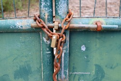 Metal gate locked by a padlock and rusty chain. Rusty iron chain.
