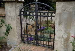 metal gate with decorative fittings in the arch garden with flowers in the yard which is entered by brick steps down. monastery garden with paths in the shape of a cross, square. surrounded by a wall