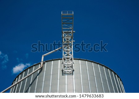 Metal grain elevator in agricultural zone. Agricultural silos against blue sky
