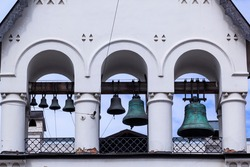 Metal green bells on white stone bell tower.