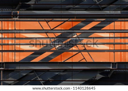 Metal grid structures over backlit bright orange wall panels. Close-up of industrial building exterior fragment. Abstract background on the subject of modern architecture or construction industry. #1140128645