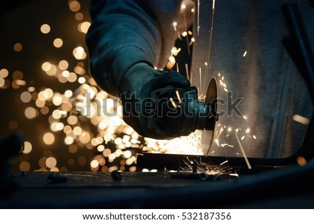 Metal grinding on steel pipe with flash of sparks close up