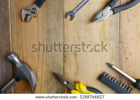 Metal hammer, screwdriver, pliers on wooden background #1288766827