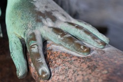 metal hand of an old bronze statue laying on