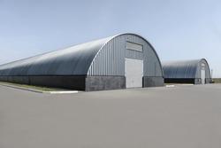 Metal hangar oval against the blue sky