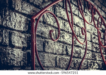 Metal headboard. An empty bedroom with a forged bed and a brick designer decorative wall. Filtered hipster image.  #596547251