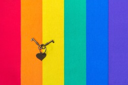 Metal heart and keys on rainbow flag pattern of fabric texture for LGBTQ. Rainbow flag of fabric texture for LGBT pride and metal keys and heart. Homosexual texture flag. Love and freedom concept.