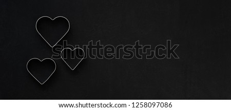 Metal hearts on a festive black background. Baking molds. Cookie cutters. Flat lay, top view #1258097086