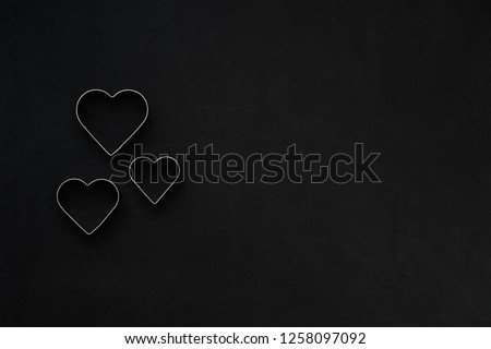 Metal hearts on a festive black background. Baking molds. Cookie cutters. Flat lay, top view #1258097092