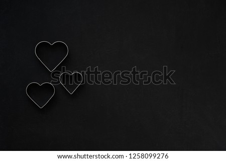 Metal hearts on a festive black background. Baking molds. Cookie cutters. Flat lay, top view #1258099276