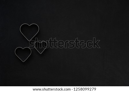 Metal hearts on a festive black background. Baking molds. Cookie cutters. Flat lay, top view #1258099279