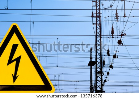Metal high voltage danger sign and railway electric overhead contact wire all over.