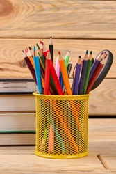 Metal holder with multicolored pencils. Stack of books and colorful pencils in basket on wooden background.