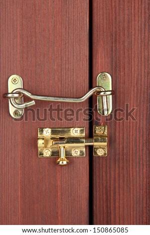 Metal hook and deadbolt in wooden door close-up