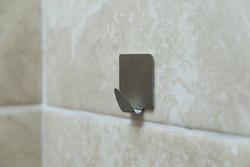 Metal hook for clothes on a tile. Wall hook for towels.