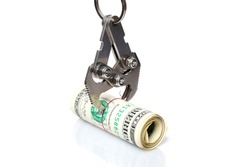 Metal hook grabs roll of American dollars. Concept of capture and retention of revenues by stock exchanges, isolated on white background with copy space