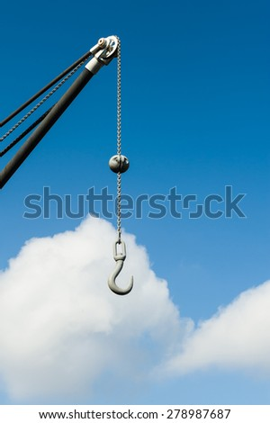 Metal hook hanging on a chain.