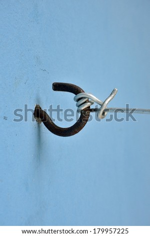 metal hook on blue wall in utility