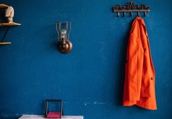 Metal hooks on the background of a blue wall. A red women's jacket is hanging on a hanger.Plaster on the wall. rough, uneven surface. Vintage background and texture.