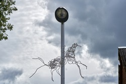 Metal horse sculpture made from vires on the lamp pole