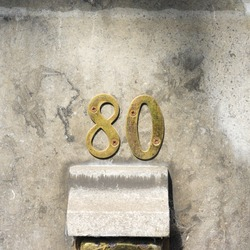 metal house number eighty on a stone wall