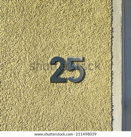 metal house number twenty five. Separate lettering on a yellow stucco wall.