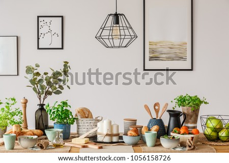 Metal, industrial ceiling lamp above a big, wooden dining table with breakfast setup