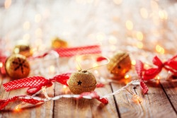 Metal Jingle Bells and Christmas Garland Light on wooden background. Christmas background