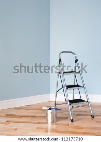 Metal ladder and a can of paint in empty room. Renovation project.