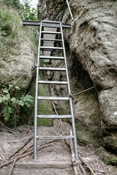 Metal ladder in mountains via ferrata. The steel cable with steel bolt anchors