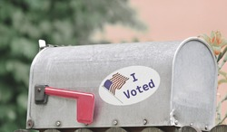 Metal mailbox for rural homes with I Voted sticker as concept for voting by mail or absentee ballot paper