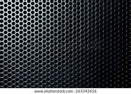 Metal mesh with round black holes close up.