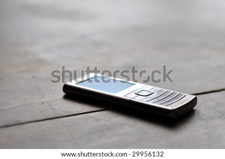 metal mobile phone on wooden table